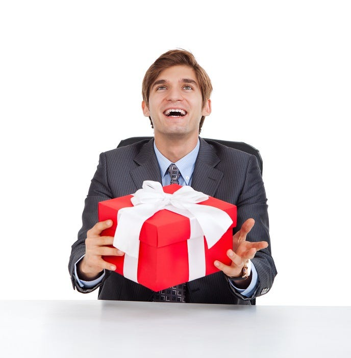 business man smile hold red present gift box with bow sitting at the desk, look up to empty copy space, isolated over white background