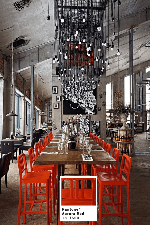 industrial-style-restaurant-interior-with-bright-red-chairs-pantone-aurora-red-min-with-square