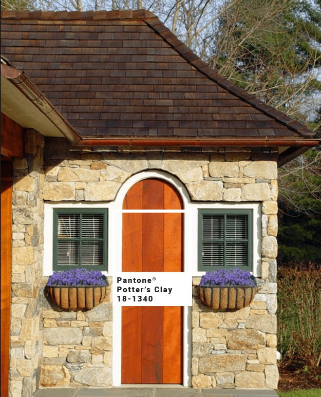 stone-cottage-with-burnt-orange-stained-wood-door-pantone-potters-clay-min-with-square