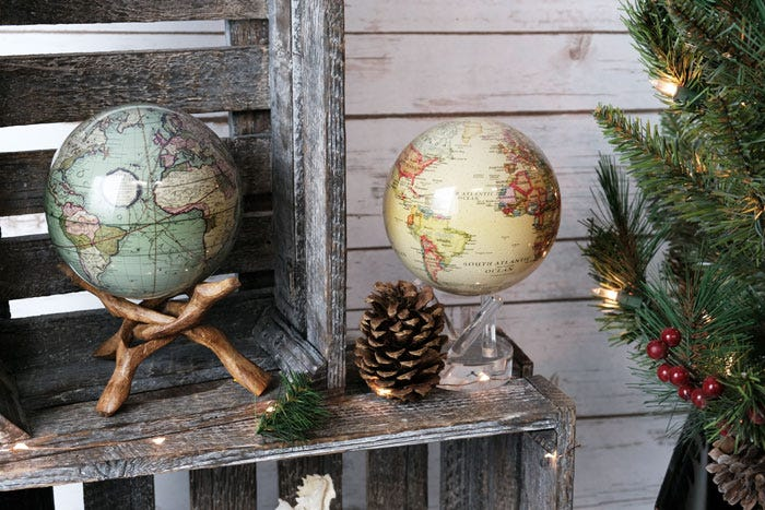 Green antique terrestrial globe and yellow political MOVA globe with christmas decor