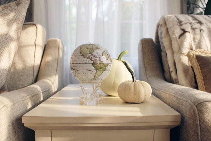 Antique terrestrial white mova globe surrounded by fall decor